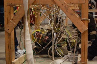 Daniel Elmore of the Malden Fire Department pulls himself through wires and ropes as part of an obstacle course that was set up at the Ladd Fire Station