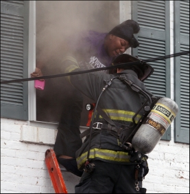 An unidentified Quincy firefighter rescues a woman from a burning second-floor window after fire broke out Wednesday morning at 633 State in Quincy. (H-W Photo/Phil Carlson) A dramatic scene unfolded late Wednesday morning after a fire broke out at at 633 State. One man was reportedly helped from the building by an unknown rescuer, and Quincy Fire Dept. Lt. Jack Ray rescued a second occupant from a second floor window. The following photographs detail Ray's rescue as it happened. (H-W Photo/Phil Carlson)